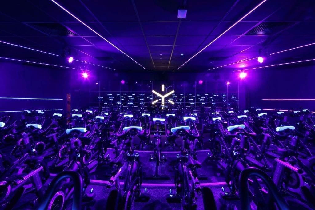 purple lit interior design of a spin studio